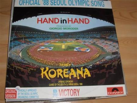 Koreana:  Hand In Hand - Brønnøysund - 1988 Gradering: Vinyl/Cover: EX - / VG POLYDOR 887 730-1 Hand In Hand is the official '88 Seoul Olympic Song. This release contains the original version of this song which was officially approved by the Seoul Olympic Organizing Committee.  - Brønnøysund
